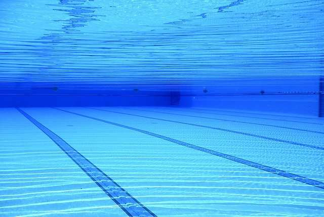 underwater view of a pool with white, striped flooring